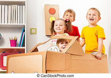 Happy little travelers driving cardboard car
