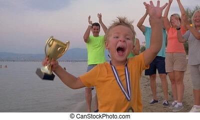 Happy little winner running with trophy