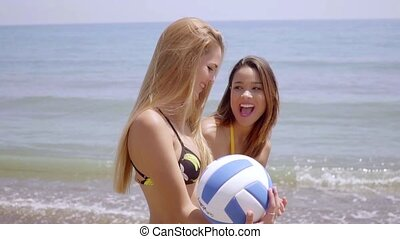 Happy lively young women playing with a beach ball - Happy...