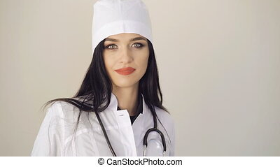 Happy look of pretty female doctor looking to camera on...