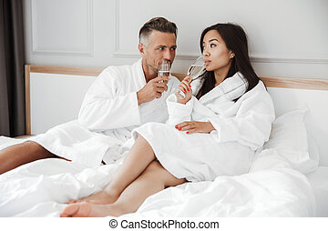 Happy lovely couple caucasian man and asian woman wearing white housecoat smiling to each other and drinking sparkling wine from glasses, while lying in bed at hotel room