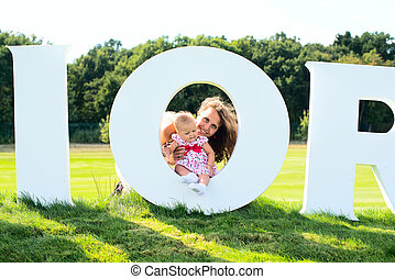 Happy lovely kid on the grass floor with the letter.  Child love clean environment