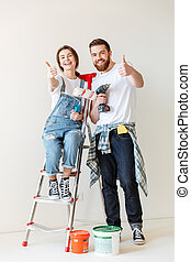 Happy lovers showing thumb up while making repair