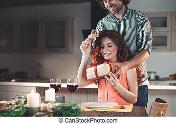 Happy loving couple celebrating anniversary in kitchen
