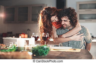 Happy loving couple cuddling during romantic dinner