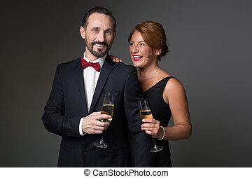 Celebrating our anniversary. Waist up portrait of joyful middle-aged man and woman standing in fancy clothing and holding glasses of alcohol drink. They are laughing. Isolated
