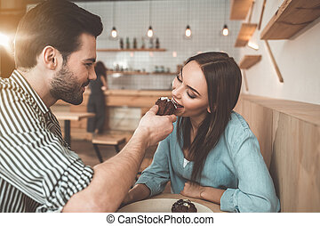 Happy loving couple eating sweet pastry