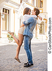 Happy loving couple. Full length of beautiful young loving couple hugging and looking at each other while standing outdoors