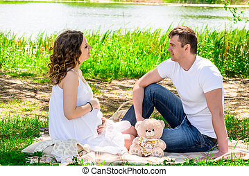 Happy loving couple in anticipation of a child resting on nature