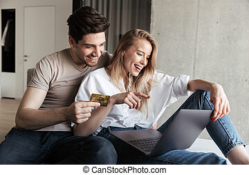 Happy loving couple in home laptop computer holding credit card.
