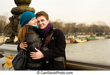 Happy loving couple in Paris hugging on the Pont Alexandre III