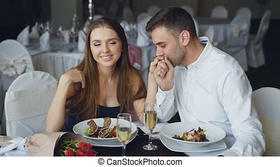 Happy loving couple is holding hands, talking and kissing during romantic dinner in restaurant. Affectionate relationship, love and fine dining concept.