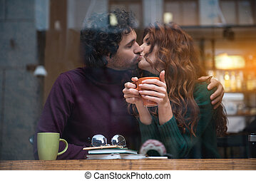 Happy loving couple kissing in cafeteria