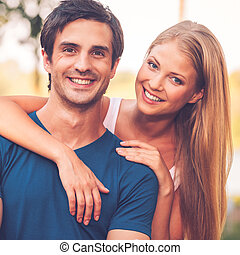 Happy loving couple. Portrait of beautiful young loving couple smiling and looking at camera while standing outdoors