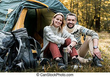 Happy loving couple resting near tent in the woods