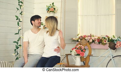 Happy loving couple sitting in swing and talking in their garden at home