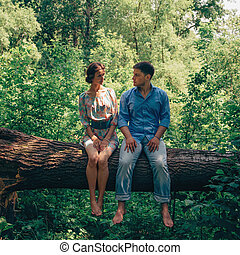 Happy loving couple sitting on tree in summer