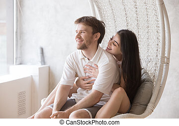 Happy loving couple sitting together in lounge hanging chair