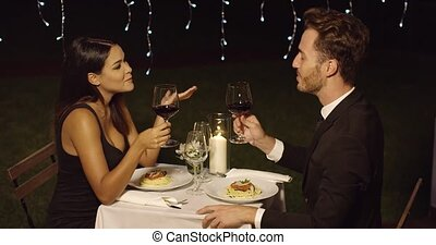 Happy loving couple toasting each other during a romantic...