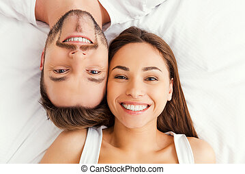 Happy loving couple. Top view of beautiful young loving couple lying in bed together and smiling