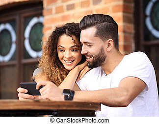 Happy loving couple using a smartphone sitting in terrace -...
