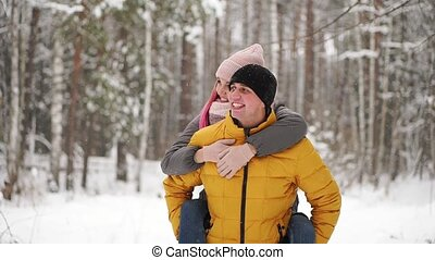 happy loving couple walking in snowy winter forest, spending...