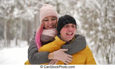 happy loving couple walking in snowy winter forest, spending christmas vacation together. Outdoor seasonal activities. Lifestyle capture