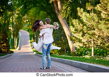 happy loving couple walking in the summer park