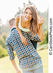 Happy loving couple. Young man holding beautiful cheerful girl on his shoulder