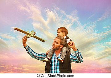 Father and son playing and having fun in the evening at sunset