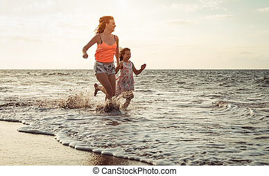 Happy loving family mother and daughter running on the beach at sunset - Mum having fun with her kid long sea shore during summer holidays - Parent vacation time lifestyle concept