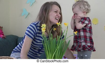 Mother and daughter look at houseplants and narcissus...