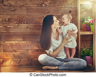 Happy loving family. Mother and her child baby girl playing...
