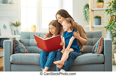 mother reading a book to her daughters