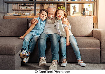 Happy loving grandfather cuddling grandchildren on couch