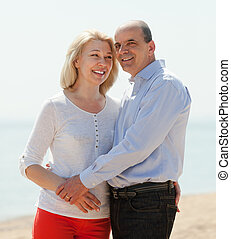 happy loving mature couple against sea
