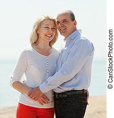 happy loving mature couple against sea