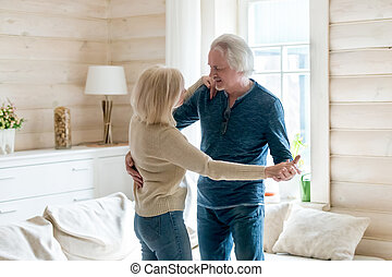 Happy loving mature couple dancing at home in living room