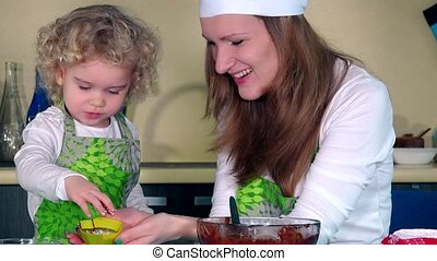Happy loving mother and daughter preparing cupcakes in kitchen