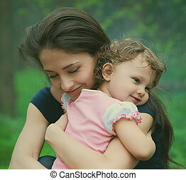 Happy loving mother and girl cuddling outdoor summer background