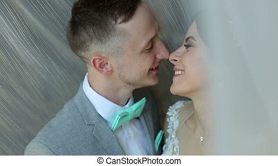 Happy loving newlyweds stand in an embrace near the window and kiss gently.