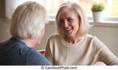 Happy loving older couple having fun talking on date,...