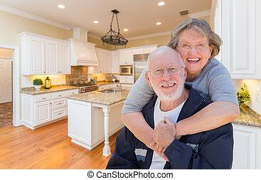 Senior Couple Hugging Inside Custom Kitchen
