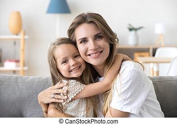 Happy loving young mother hugging little preschool daughter, por