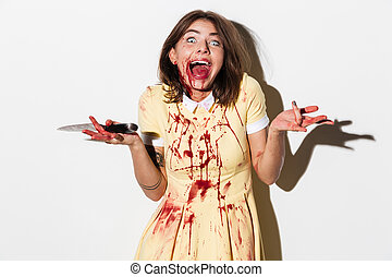 Happy mad zombie woman holding a knife