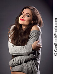 Happy makeup woman with red lipstick hugging herself with natural emotional enjoying face in grey fashion sweater. Love concept of yourself on dark shadow background. Closeup portrait