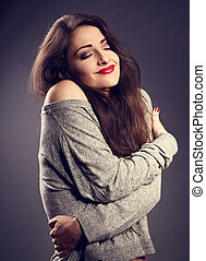 Happy makeup woman with red lipstick hugging herself with natural emotional enjoying face in grey fashion sweater. Love concept of yourself on dark shadow background. Toned closeup portrait