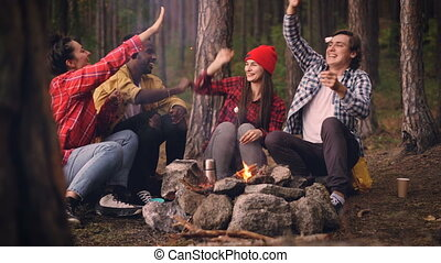 Happy male and female friends are doing high-five and eating...