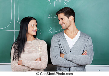 Happy male and female students with arms crossed looking at each other against chalkboard