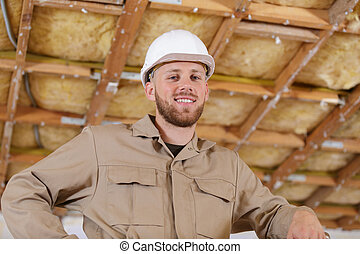 happy male builder in a helmet looking at camera